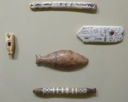 Picture 2: Artifacts, one of which is an amulet showng a man ice fishing. You can see the fish underwater. It is drawn in tradtional Inupiaq graphic language.